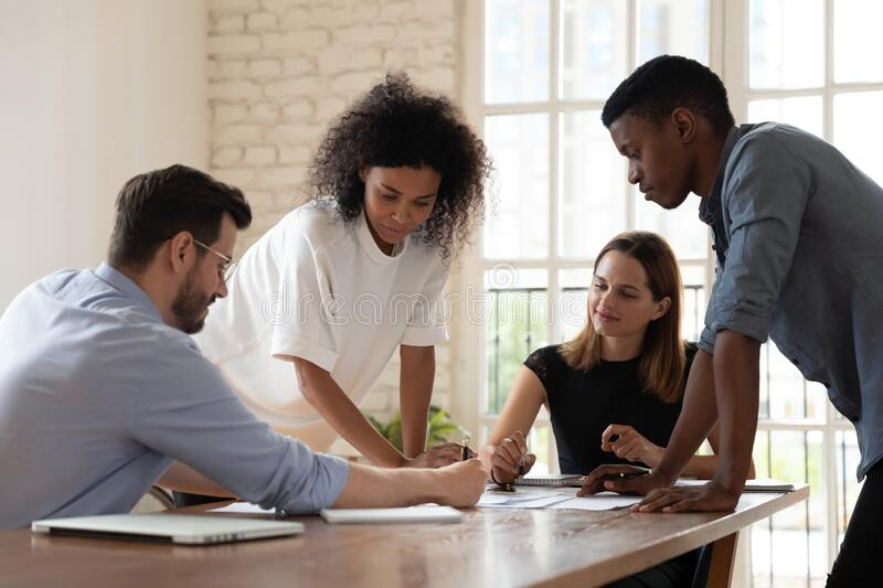 Serious focused diverse employees team working with documents together royalty free stock photos