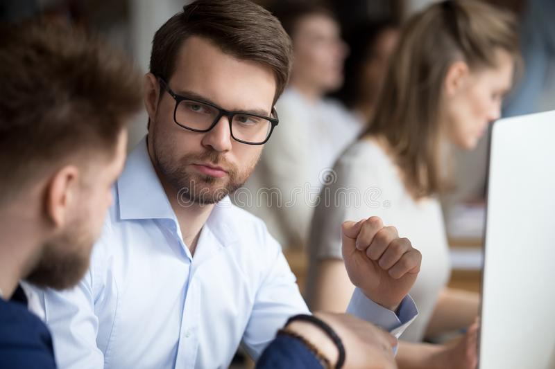 Serious focused male employee listening to colleague. Serious focused male employee in glasses attentively listening to colleague, looking at boss, director royalty free stock photography