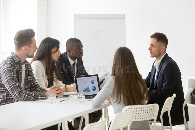 Serious focused multi-ethnic team listening to leader speaking a. Serious multi-ethnic team listen to leader speaking at meeting, focused ceo boss coach talking royalty free stock photos