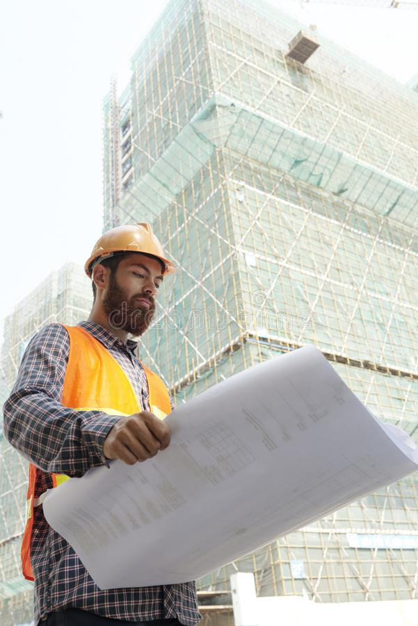 Serious foreman with blueprint stock photo