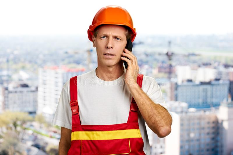 Serious foreman talking on phone. stock image