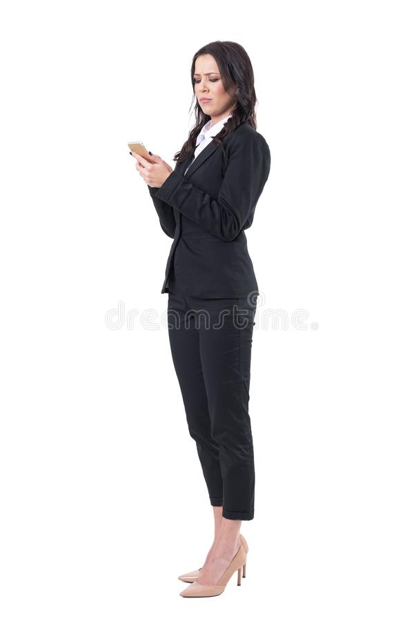Serious frustrated business woman in black suit using mobile phone. royalty free stock photo