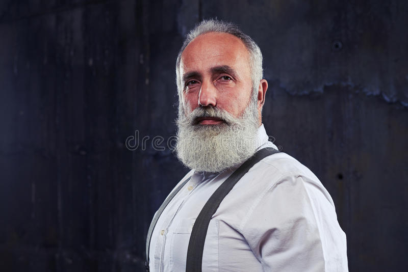 Serious gaze of mature man looking directly at the camera isolated over black background royalty free stock images