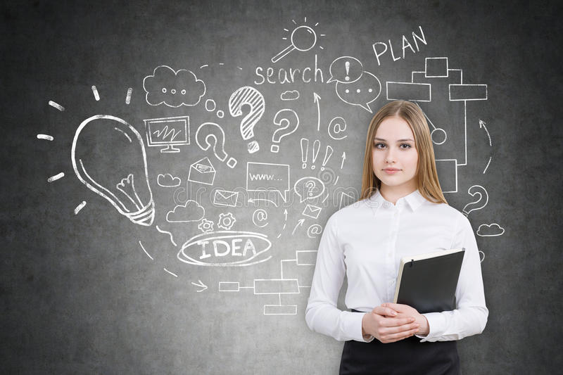 Serious girl with black folder and startup idea sketch. Serious woman with black folder is standing near blackboard with startup idea sketch on it. Concept of royalty free stock image