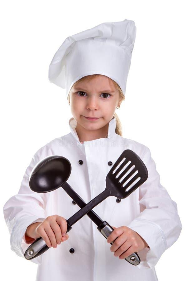Serious girl chef white uniform isolated on white background. Holding black ladle and scapula crossed. Portrait image stock image
