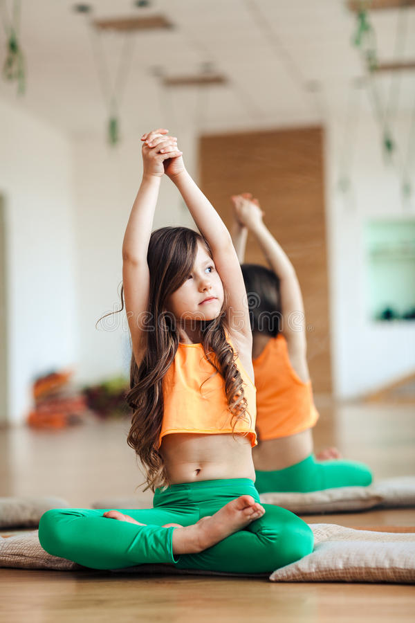 Serious girl child practicing yoga, indoor full length, Bright room background stock photography