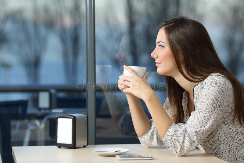 Serious girl looking through a window in a coffee shop stock photos