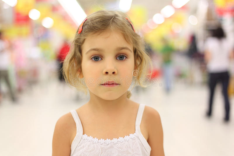Serious girl standing in big store alone royalty free stock photos