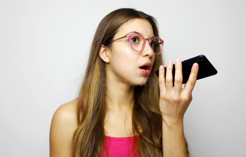 Serious girl using voice recognition app on smart phone stock photos