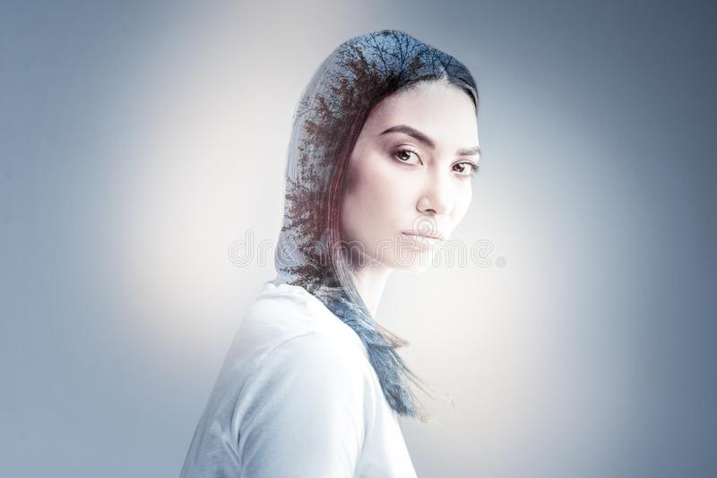 Enigmatical brunette raising her eyebrows. Serious glance. Attractive young woman standing in semi position and pressing lips while looking at camera royalty free stock images