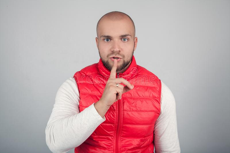 Serious good looking male with bald hair, keeps fore finger on lips, tries to keep conspiracy, looks aside, says: Shh, make stock images