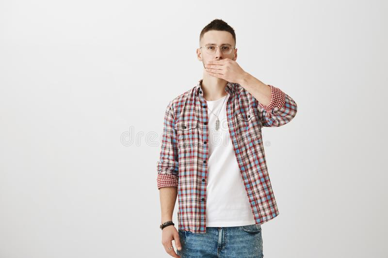 Serious good-looking male model in glasses and trendy checked shirt covering mouth with palm and staring at camera over royalty free stock photography