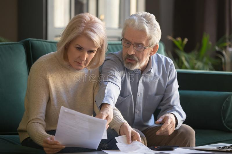 Serious grey haired mature couple calculating bills, checking finances together stock image
