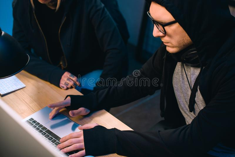 Serious hacker working on new malware with accomplice. In dark room royalty free stock images