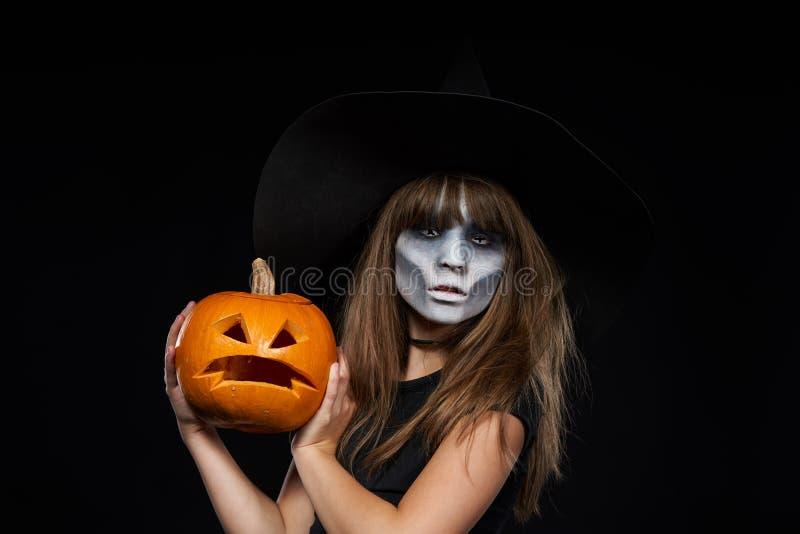 Serious Halloween witch holding Jack-O-Lantern pumpkin looking at camera stock image