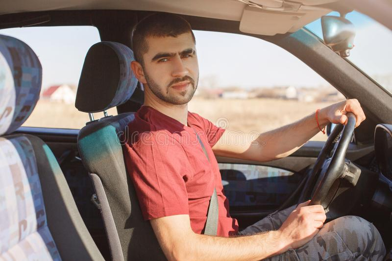 Serious handsome bearded male driver poses in his car, rides auto, uses safety belt, being experienced, looks confidently at camer stock photos