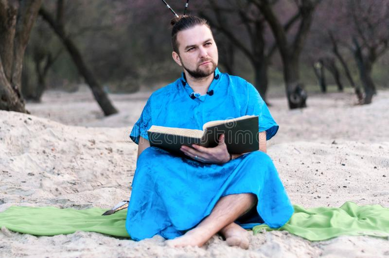 Serious handsome bearded man in blue kimono sitting, holding opened large book royalty free stock photos