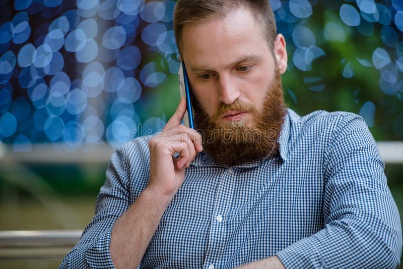 Serious handsome bearded young caucasian man in shirt calling holding cell phone standing indoors with background with blue bokeh stock image