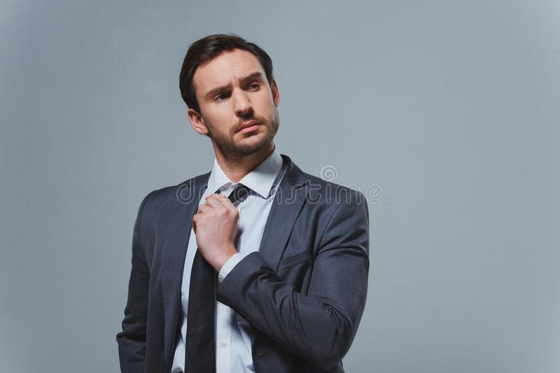 serious handsome businessman fixing tie stock images