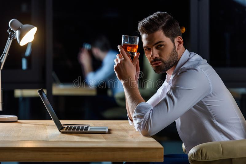 serious handsome businessman sitting at table and holding glass royalty free stock photos