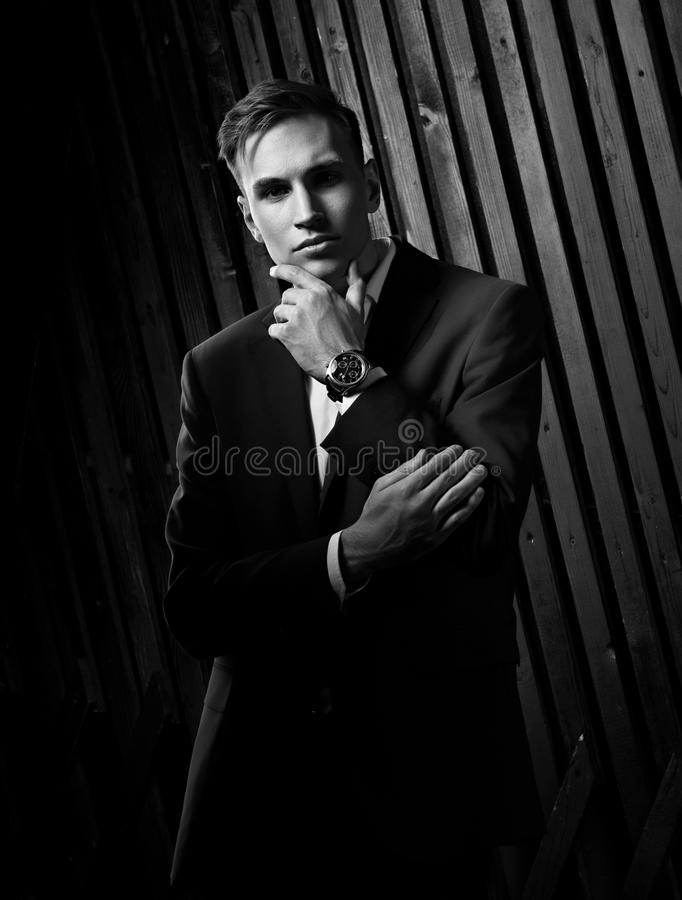 Serious handsome man with strained look posing in blue fashion s. Uit and white style shirt and fashion watch on the hand on black wall wooden background. Black royalty free stock photography