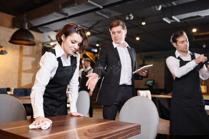 Handsome manager giving recommendations about cleanup to waitres. Serious handsome manager with tablet pointing at table while giving recommendations about stock images