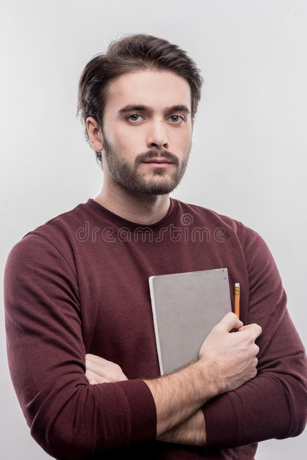 Serious handsome office manager holding notebook and pencil stock photos