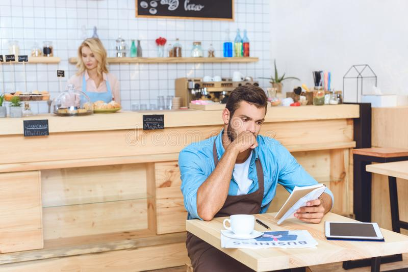 serious handsome small business owner holding notebook while waitress stock photography