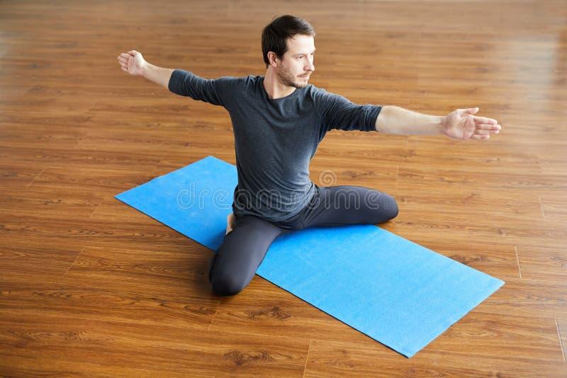 Supple man practicing yoga royalty free stock image
