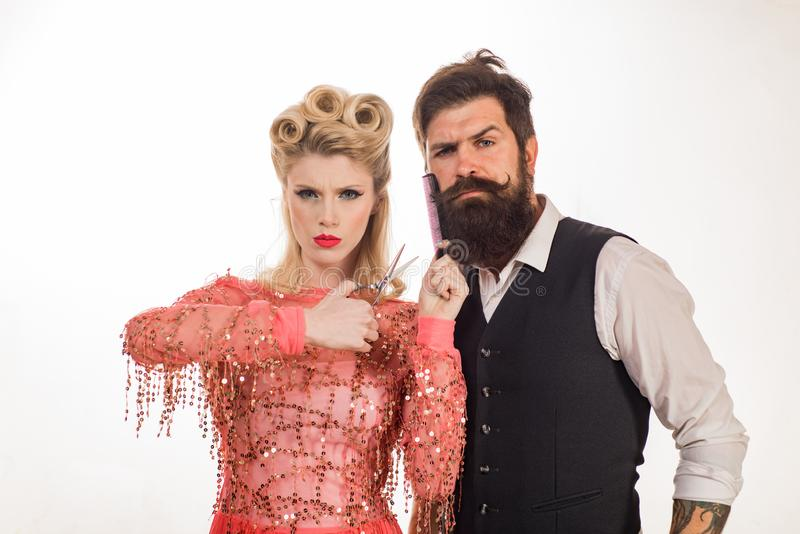 Serious hipster man with beard and woman with scissors. Barber. Beautiful woman cut beard. Couple in barbershop on royalty free stock images