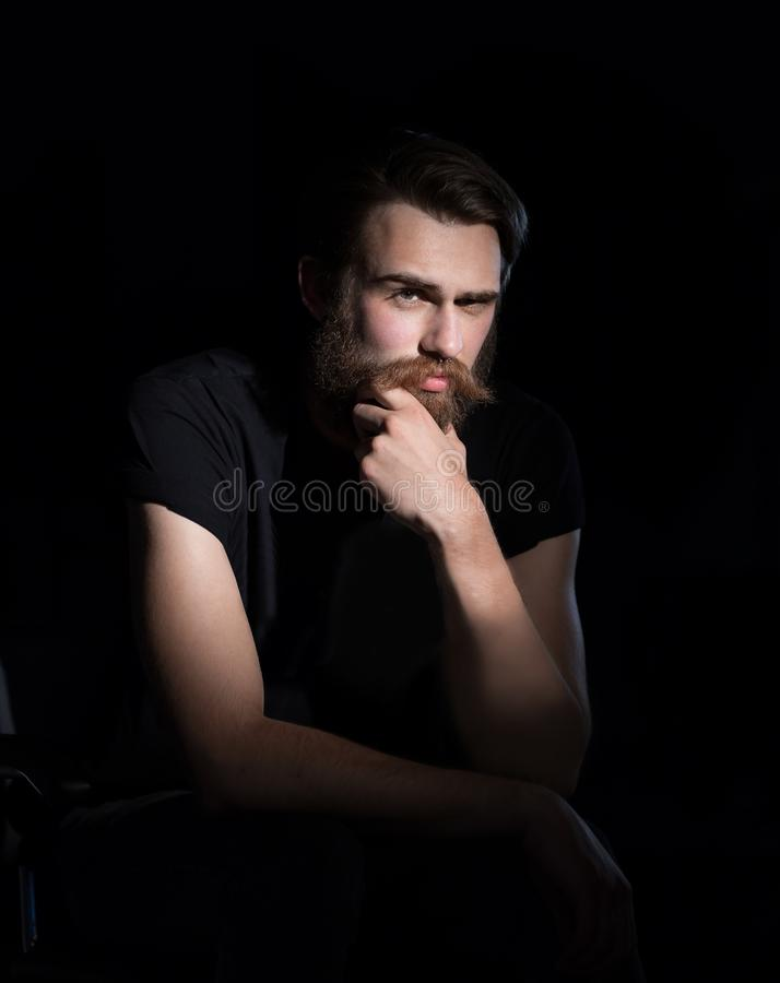 Serious hipster man sitting in a chair. royalty free stock images