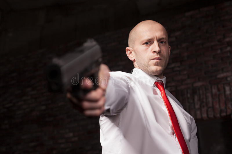Serious hired murderer in red tie aims a gun. Professional secret agent concept. Assassin with guns, wallpaper, background or poster. Contract killer with royalty free stock images