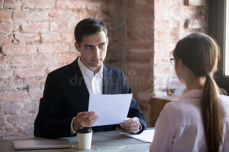 Serious HR manager interviewing young woman student stock images