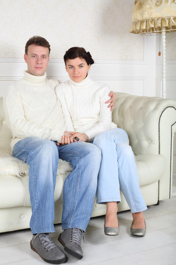 Serious husband and wife hug and look at camera. On white sofa at home royalty free stock photos