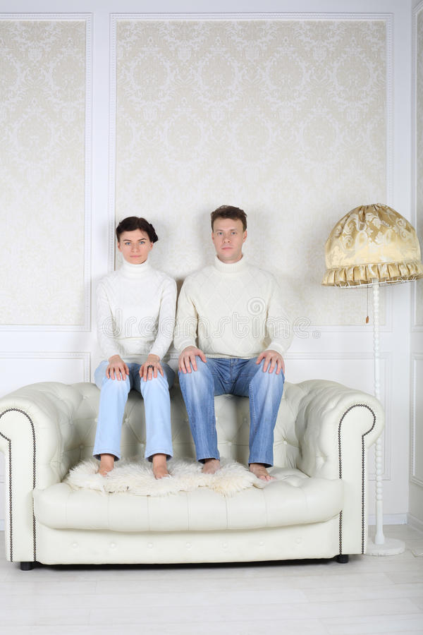 Serious husband and wife sits on back of white leather sofa. At home stock photography