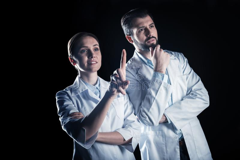 Serious intelligent scientists standing against black background stock photography