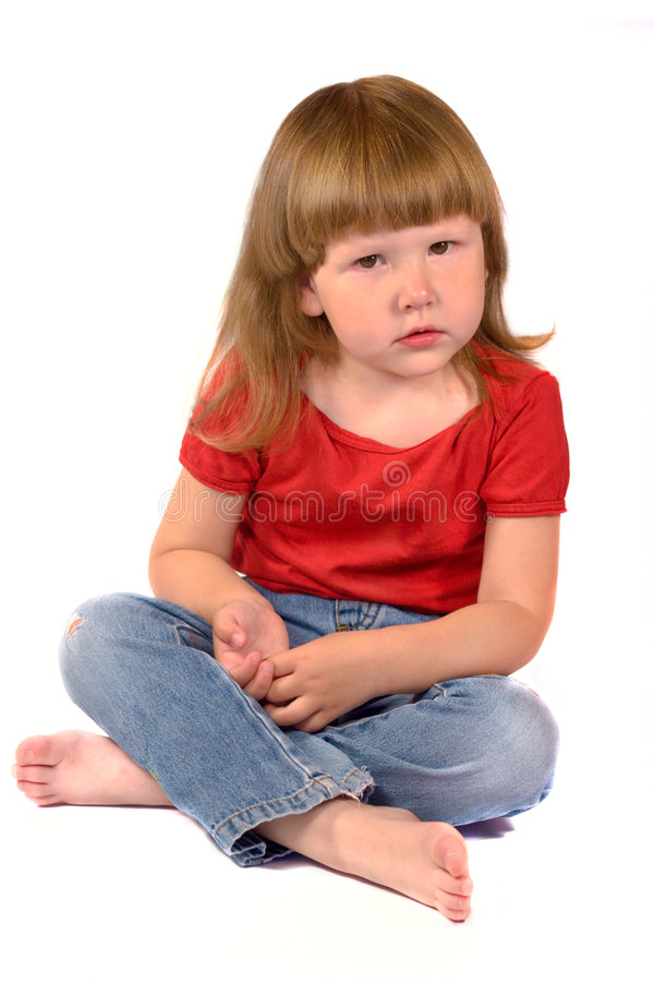 Serious kid. Sitting on the floor isolated on white stock images