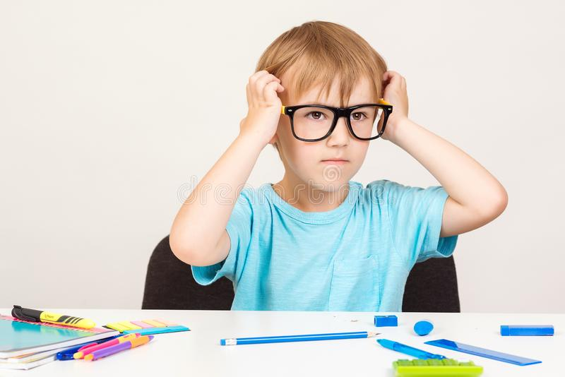 Serious kid in eyeglasses is sitting at a desk. Little child writing with colorful pencils, indoors. Elementary school and stock photos