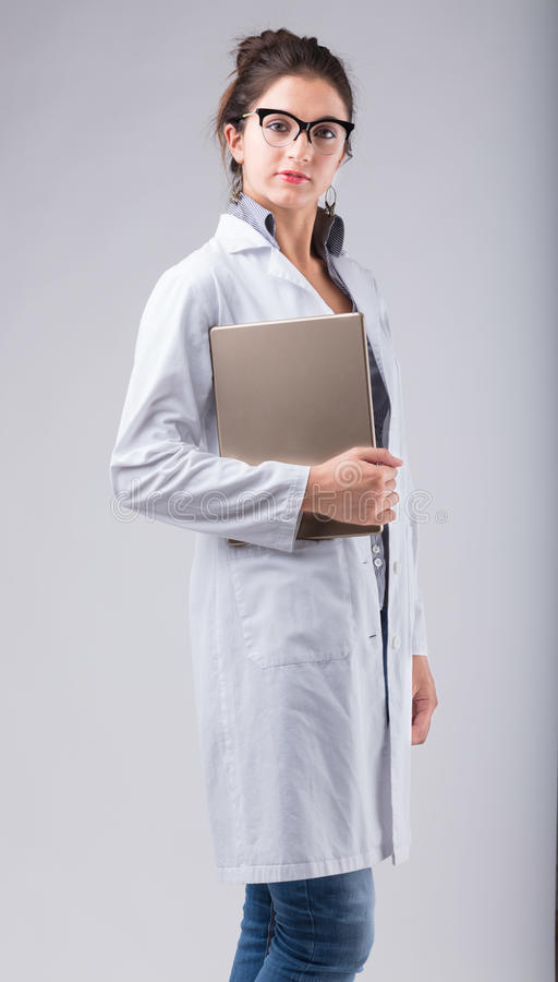 Serious lady doctor carrying a tablet stock photography