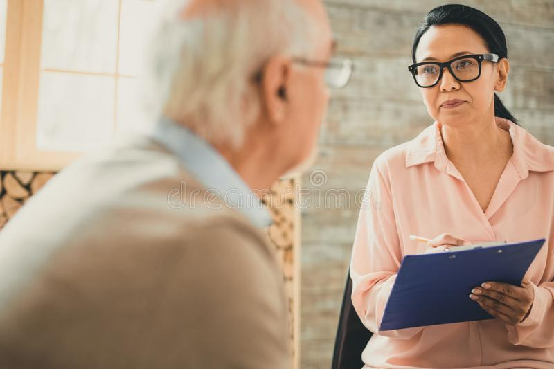 Serious lady in office style cloths having meeting with ward. Listing all information. Serious lady in office style cloths having meeting with her old ward while royalty free stock photo