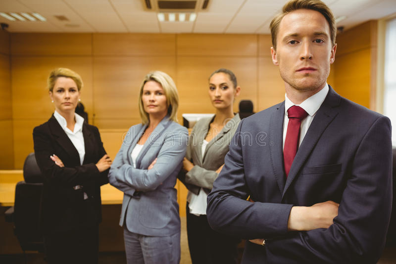 Serious lawyer standing with arms crossed. In the court room stock photography