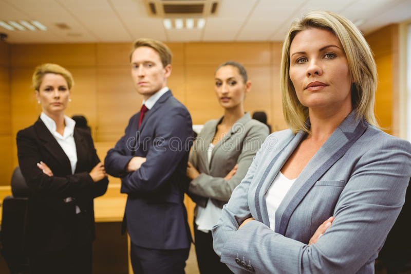 Serious lawyer standing with arms crossed. In the court room royalty free stock photos