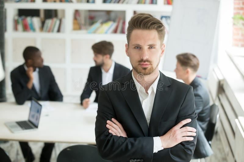 Serious leader in suit looking at camera with executive team royalty free stock images