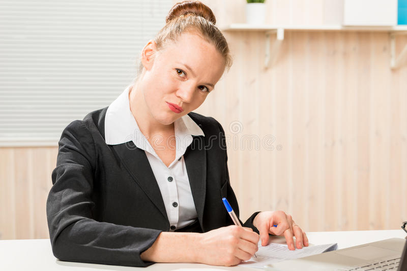 Serious leader woman posing signature. On important documents stock photos