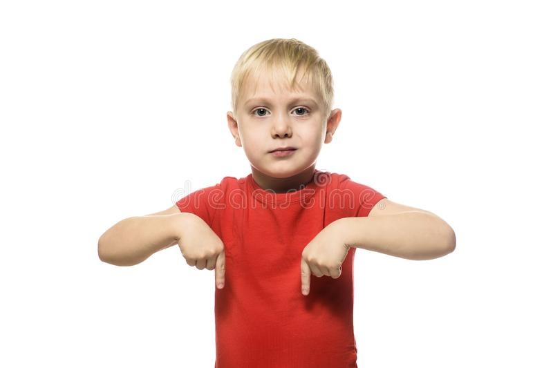 Serious little blond boy in a red shirt stands and shows index fingers down. Isolate on white background royalty free stock photos