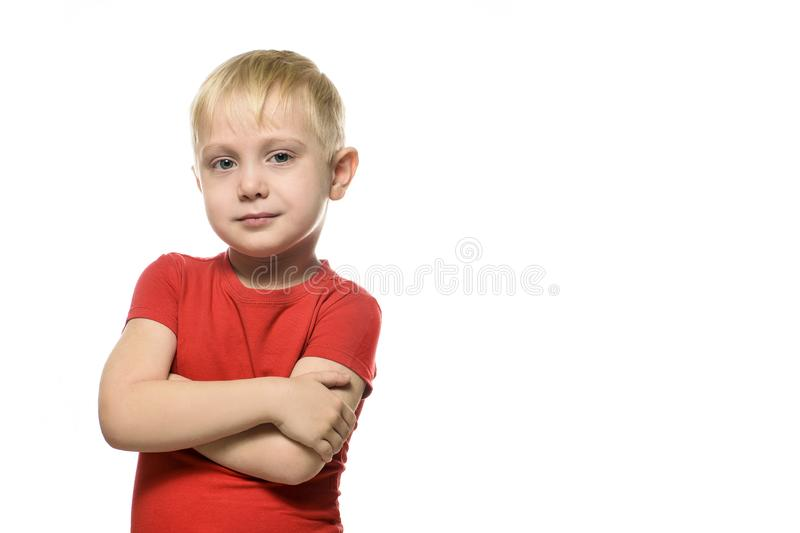 Serious little blond boy in a red t-shirt stands with folded arms. Isolate on white background.  stock image
