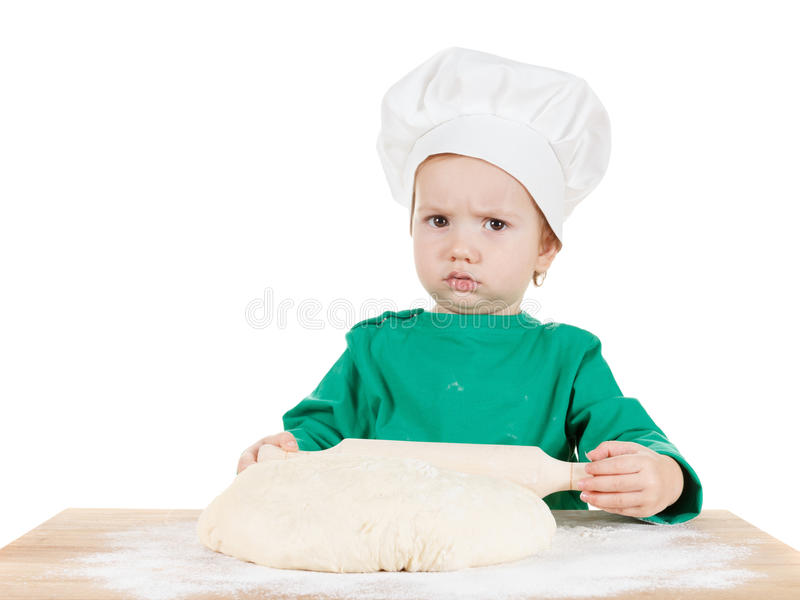 Serious little boy kneading dough for the cookies, isolated on white stock photos