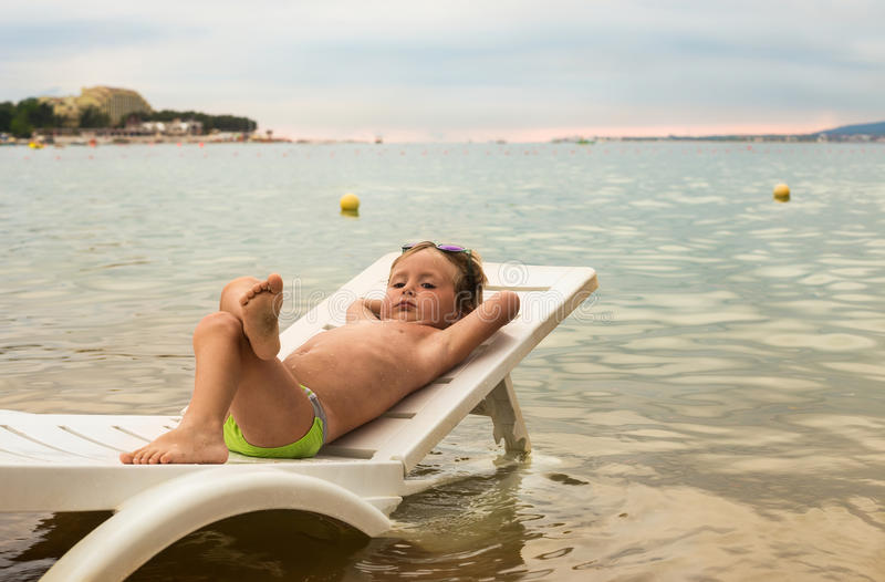 Serious little boy resting on lounger by sea at sunset. Serious little boy resting on a lounger by the sea at sunset stock photos