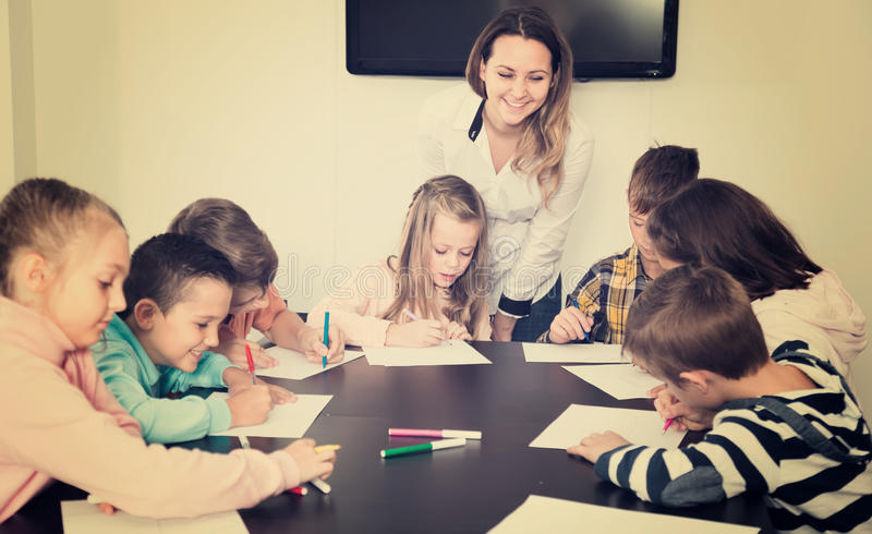 Serious little children with teacher drawing in classroom royalty free stock photos