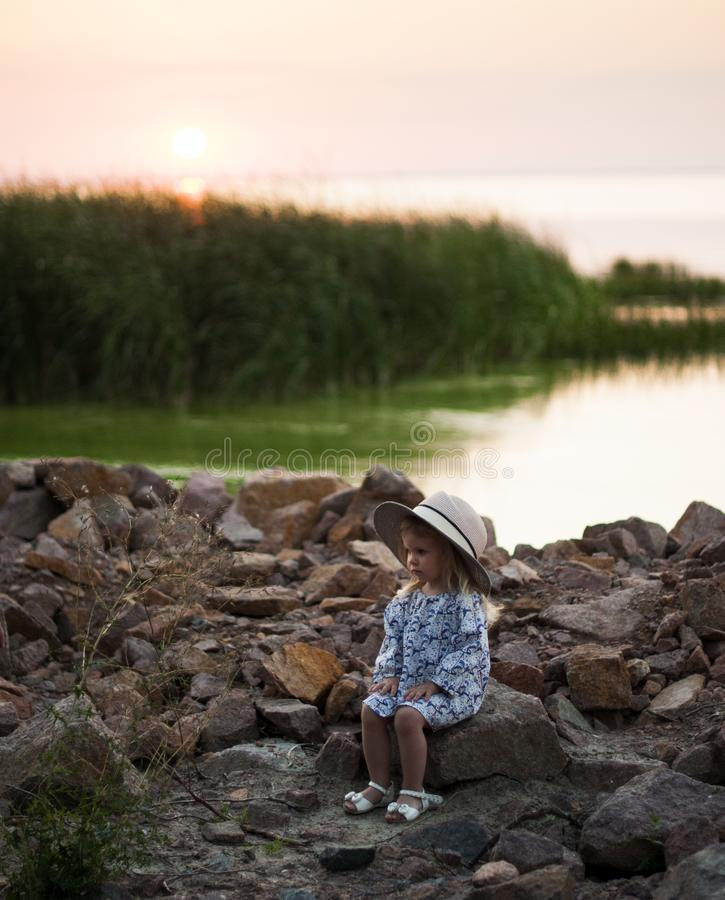 A serious little girl in a hat sits on a stony bank near a river stock photos